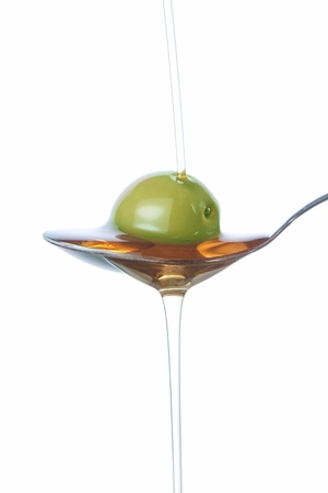 Olive on the spoon, pouring with oil