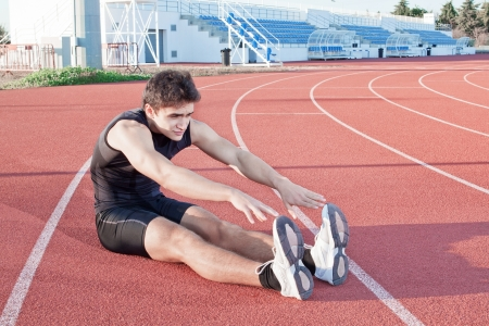 A young man makes an athlete stretching  Against the background the stadium  photo
