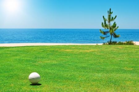 drapeau portugal: Une balle de golf sur l'herbe verte avec le Portugal océan