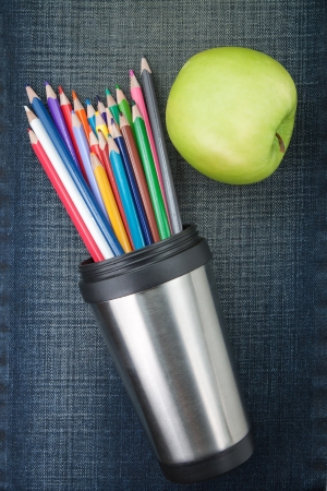 Container pencil on the background jeans and an apple. Stock Photo - 14873439