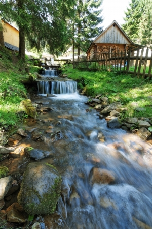Mountain stream flowing beside houses  photo