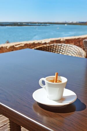 A cup of coffee with a stick Canela on the table outside  Stock Photo