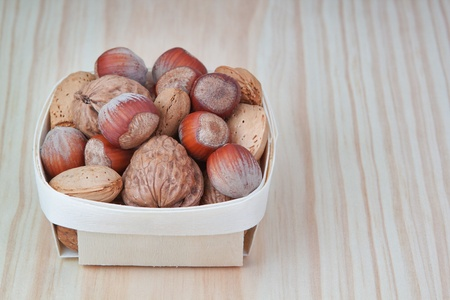 Basket with wood, walnuts and almonds  On a wooden texture  photo