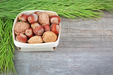 Christmas basket with wood, walnuts and almonds  On a wooden texture Stock Photo - 15716549