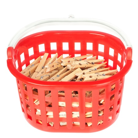 Set of pegs clothespins in the red basket. On a white background. photo