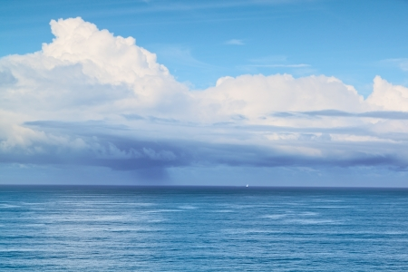 Small sailboat at sea before the storm in the rain  photo