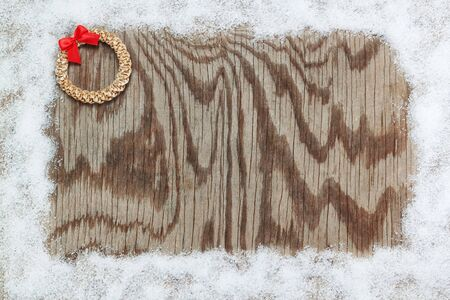 Snow frame and straw wreath with a bow on a wooden texture. For Christmas. photo