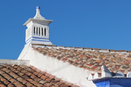 Old Portuguese chimney and tile  Against the blue sky