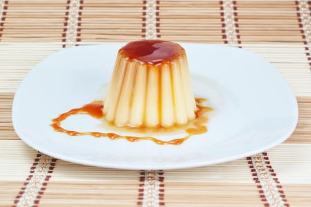 flan: Yogurt-pudding on a plate on decorative wooden napkin