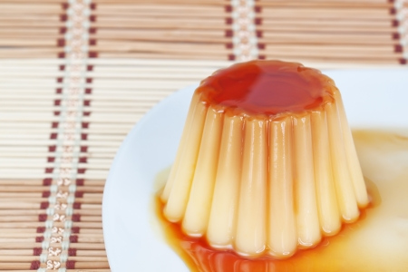 flan: Close-up of yogurt pudding on a plate on decorative wooden napkin