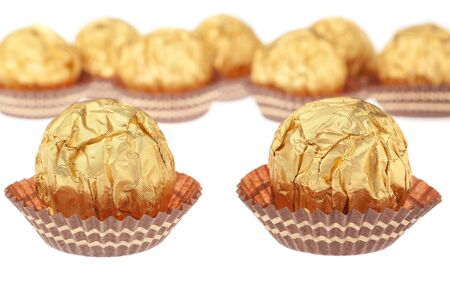 Group chocolate candies wrapped in gold. On a white background. photo