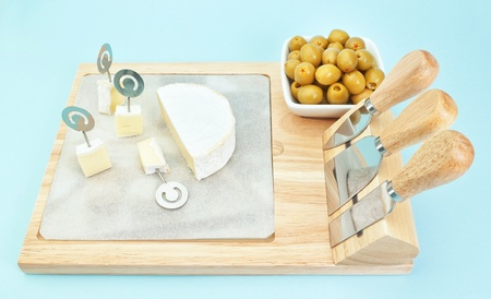 Sliced ​​cheese on a wooden board in a set of black olives  photo