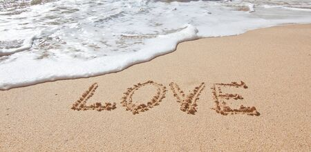 The word love in the sea on the beach in Valentine Day. Closeup. photo