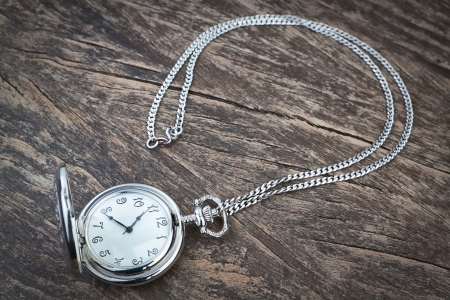 Silver pocket watch on a chain, a wooden texture  Conceptual photography  photo