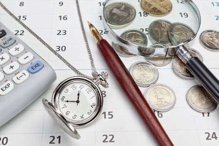 Office supplies and pocket watches  Against the background of the calendar  photo