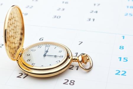 Antique pocket watch on a calendar