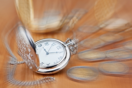 Pocket watch against the background of the euro coins, in focus  photo