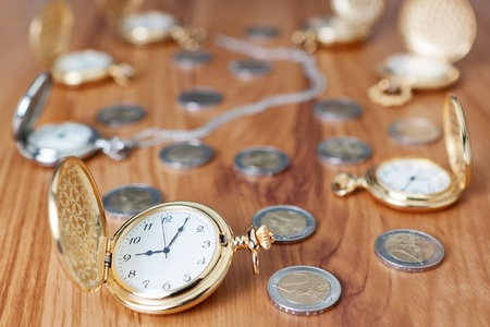 Group gold pocket watch against the euro coins  photo