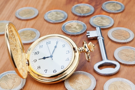 Gold pocket watch on the background euro coins and keys  photo