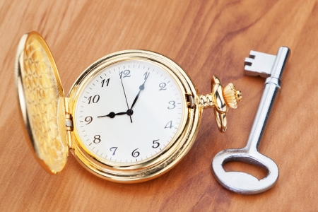 Gold pocket watch and key  Against the background of a wooden texture  photo