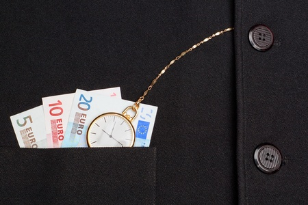 Concept photo of a pocket watch in a jacket on a background of money euro  photo