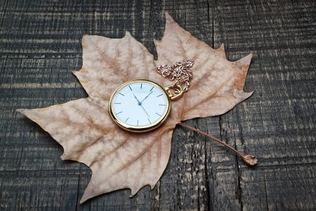 Pocket watch the autumn leaves  On a wooden texture  photo