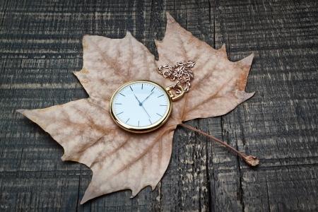 reloj antiguo: Reloj de bolsillo las hojas de otoño en una textura de madera
