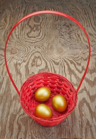 Golden Easter eggs in a red basket. On a wooden texture. photo