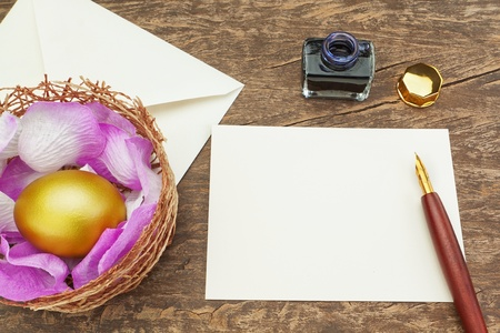Easter golden egg near the pen to write the letter. photo