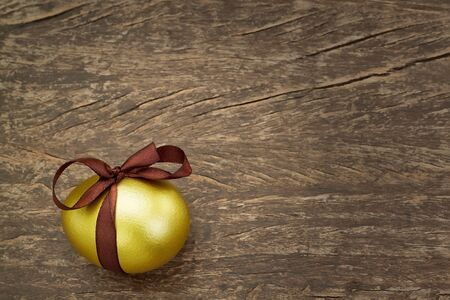 Easter golden egg with a brown ribbon, on a wooden texture. photo