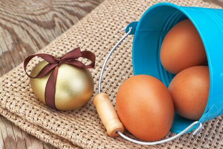 Blue bucket and easter golden eggs scattered on sackcloth. photo