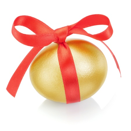 Golden easter egg with red bow. On a white background. photo
