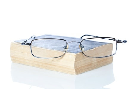 Glasses on old used books. On a white background. Isolated. photo
