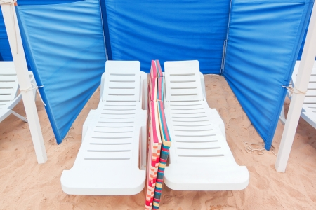 Sun loungers on the sand, and fencing for the wind. photo