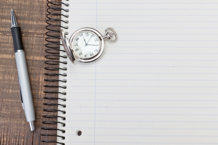 Antique pocket watch on notebook for notes. On textured wood. photo