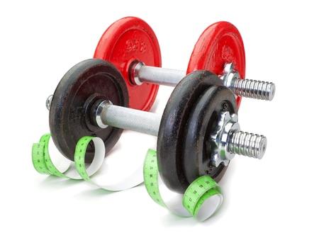 metro de medir: Dos pesas de gimnasia para la aptitud y la m�trica de medici�n sobre un fondo blanco