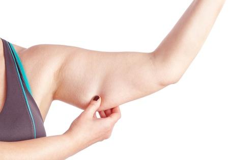 mujeres gordas: Mujer de mediana edad la celebraci�n de una mano con el exceso de grasa. En un fondo blanco. Foto de archivo