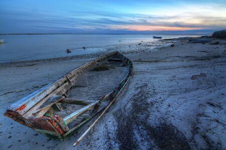 Old abandoned broken boat at sea against sea landscape. photo