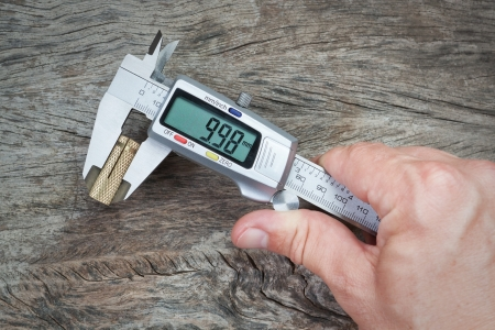 Man measuring caliper detail on a wooden background. Close-up. photo