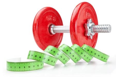 metro de medir: Mancuernas de fitness y deporte con un metro de medici�n sobre un fondo blanco. Close-up. Foto de archivo