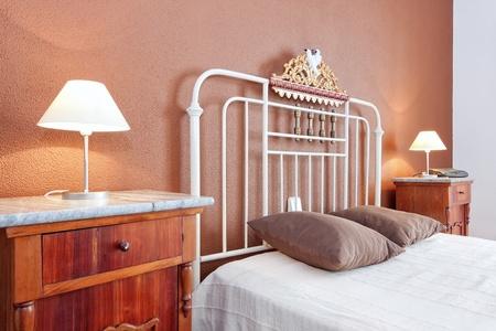 abatjour: Paralumi vicino il vecchio letto classico in camera da letto. Colore marrone. Archivio Fotografico