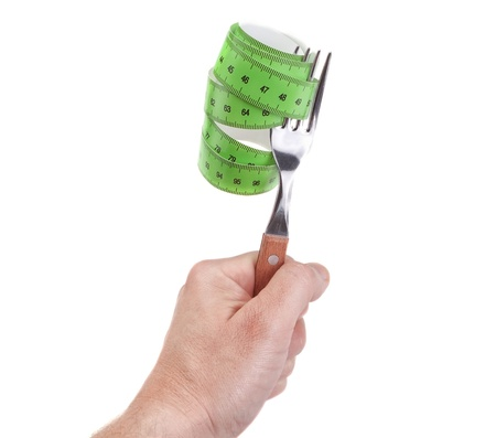 Fork in hand and a coiled measuring meter, symbol diet  photo