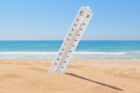 heat wave: A thermometer on the beach near the sea to check the temperature.