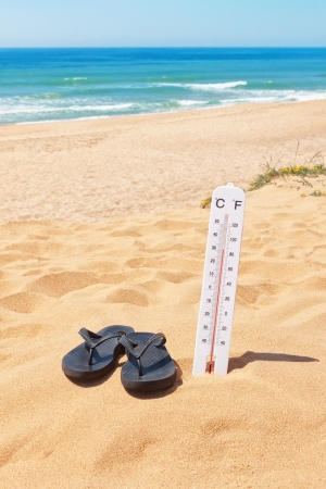 Slippers on the beach beside the thermometer and the sea. Summer. Imagens