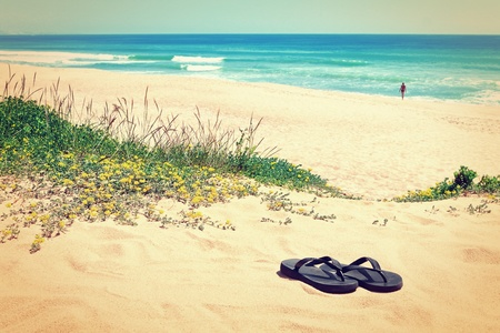 Slippers on the background of the beautiful beach and the sea. In the warm colors. photo