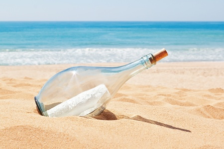 A bottle with a letter of distress on the beach. Summer. photo
