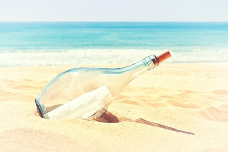 A bottle with a letter of distress in the sand on the beach. In the summer and warm colors. photo