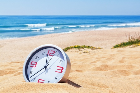 sands of time: Classic analog clocks in the sand on the beach near the sea. For the holidays. Stock Photo