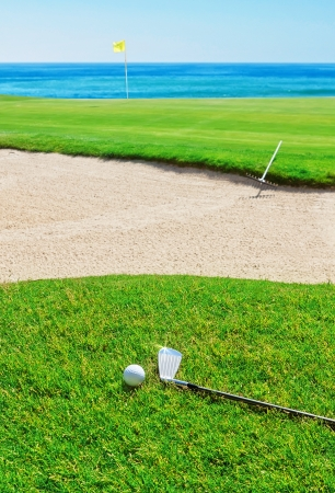 Golf stick on the grass field and ball on the background of the sea. photo
