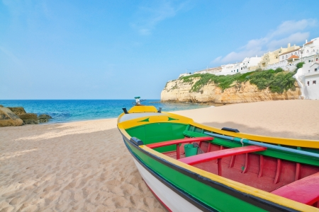 travel features: Magnificent beach on the coast of Portugal at Villa Carvoeiro. Fishing boat in the foreground.